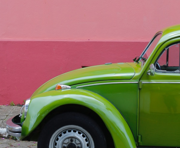 green car against pink wall